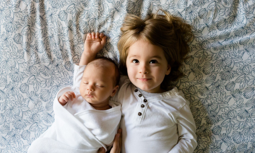 Young Girl and Baby Laying in Bed