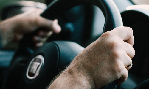 Close Up of Driver's Hands on Wheel
