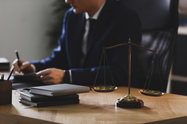 Lawyer Sitting at Desk with Scales of Justice
