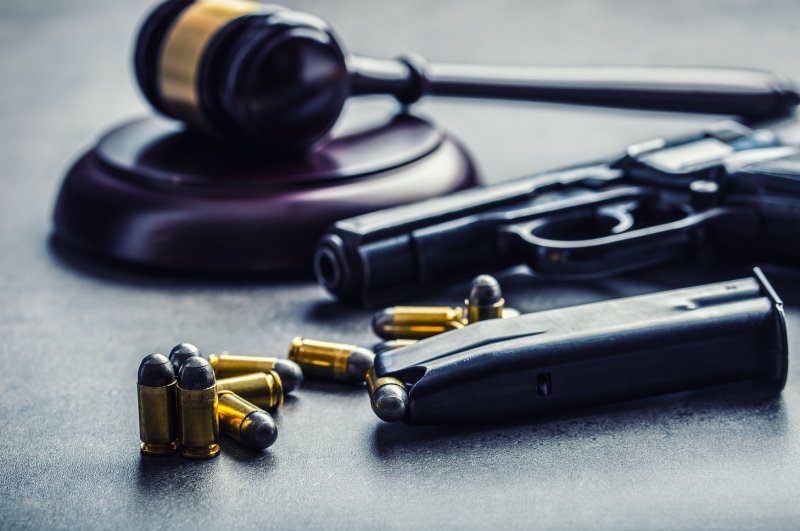 Gun with Bullets in front of Wooden Gavel